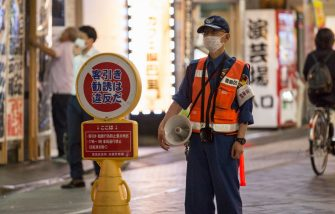 TOKYO, JAPAN - AUGUST 04: A security worker wearing face mask  is seen on August 04, 2020 in Tokyo, Japan. Japan has seen a surge in Covid-19 coronavirus cases in recent weeks with new infection rates in Tokyo regularly topping 300 per day. Although the central government continues to rule out a new nationwide state of emergency, Okinawa has imposed a prefecture-wide state of emergency and asked people to stay home for two weeks while a number of other prefectures are considering local restrictions to curb infections.  (Photo by Yuichi Yamazaki/Getty Images)