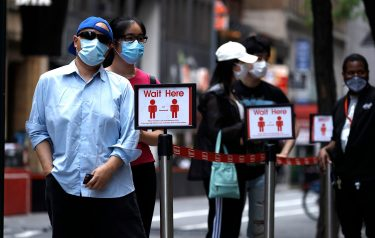 NEW YORK, NEW YORK- AUGUST 22: People wearing protective masks wait in line at designated social distancing points as the city continues Phase 4 of re-opening following restrictions imposed to slow the spread of coronavirus on August 22, 2020 in New York City. The fourth phase allows outdoor arts and entertainment, sporting events without fans and media production. (Photo by John Lamparski/Getty Images)
