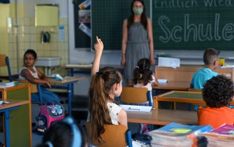 A student raises her hand in a classroom at the Petri primary school in Dortmund, western Germany, on August 12, 2020, amid the novel coronavirus COVID-19 pandemic. - Schools in the western federal state of North Rhine-Westphalia re-started under strict health guidelines after the summer holidays. (Photo by Ina FASSBENDER / AFP) (Photo by INA FASSBENDER/AFP via Getty Images)