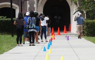 TAMPA, FL - AUGUST 21: Students attending Hillsborough High School wait in line to pickup laptops for remote learning before the first day of classes next Monday on August 21, 2020 in Tampa, Florida. Hillsborough County Schools are issuing one device per family for students who are doing remote learning during the COVID-19 pandemic. (Photo by Octavio Jones/Getty Images)