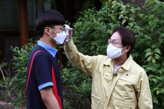 SEOUL, SOUTH KOREA - MAY 20: Cho Hee-yeon, Seoul Metropolitan office of education superintendent checks the temperature of student while back to school at Kyungbock high school on May 20, 2020 in Seoul, South Korea. Senior high school students are able to return to school from today, as South Koreans take measures to protect themselves against the spread of coronavirus (COVID-19). South Korea's education ministry announced plans to re-open schools starting for senior high school students, more than two months after schools were closed in a precautionary measure against the coronavirus. (Photo by Chung Sung-Jun/Getty Images)