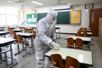 SEOUL, SOUTH KOREA - MAY 11: Disinfection professionals wearing protective clothing spray anti-septic solution at classroom to prevent the spread of the coronavirus (COVID-19) ahead of school re-opening on May 11, 2020 in Seoul, South Korea. South Korea's education ministry announced plans to re-open schools starting from May 13, more than two months after schools were closed in a precautionary measure against the coronavirus. Coronavirus cases linked to clubs and bars in Seoul's multicultural district of Itaewon have jumped to 54, an official said Sunday, as South Korea struggles to stop the cluster infection from spreading further. According to the Korea Center for Disease Control and Prevention, 35 new cases were reported. The total number of infections in the nation tallies at 10,909. (Photo by Chung Sung-Jun/Getty Images)