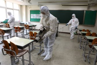 SEOUL, SOUTH KOREA - MAY 11: Disinfection professional and government official wearing protective clothing spray anti-septic solution at classroom to prevent the spread of the coronavirus (COVID-19) ahead of school re-opening on May 11, 2020 in Seoul, South Korea. South Korea's education ministry announced plans to re-open schools starting from May 13, more than two months after schools were closed in a precautionary measure against the coronavirus. Coronavirus cases linked to clubs and bars in Seoul's multicultural district of Itaewon have jumped to 54, an official said Sunday, as South Korea struggles to stop the cluster infection from spreading further. According to the Korea Center for Disease Control and Prevention, 35 new cases were reported. The total number of infections in the nation tallies at 10,909. (Photo by Chung Sung-Jun/Getty Images)