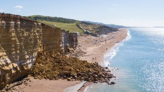 "BURTON BRADSTOCK, DORSET - AUGUST 30: Aerial view of the 9,000 ton cliff fall on August 30, 2020 in Burton Bradstock, Dorset. The fall happened at Hive Beach near the village of Burton Bradstock, Dorset Council said. Fire crews using thermal imaging equipment were called in to check for any trapped casualties but nothing was found. The council described it as a ""huge"" rock fall and said recent heavy rain had made cliffs unstable. (Photo by Finnbarr Webster/Getty Images)"
