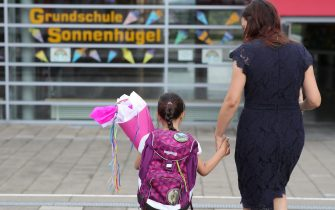 OBERPLEIS, GERMANY - AUGUST 13: First graders arrive with goodie bags for their first introductory day to school during the coronavirus pandemic on August 13, 2020 in Oberpleis near Bonn, Germany. Classes at schools across Germany are beginning this month with face mask requirements varying by state. Coronavirus infection rates are climbing again in Germany, from an average of 400 new cases per day about two weeks ago up to over 1,300 in recent days, according to the Robert Koch Institute. (Photo by Andreas Rentz/Getty Images)