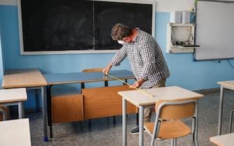 Alcuni collaboratori scolastici del liceo scientifico statale ''Isacco Newton'' sistemano i nuovi banchi singoli acquistati dalla scuola e necessari per rispettare le direttive decise dal governo per combattere la diffusione del coronavirus, Roma 25 agoso 2020.  ANSA/FABIO FRUSTACI