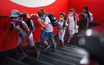 TOPSHOT - Students with face masks go upstairs to their classrooms at the Petri primary school in Dortmund, western Germany, on August 12, 2020, amid the novel coronavirus COVID-19 pandemic. - Schools in the western federal state of North Rhine-Westphalia re-started under strict health guidelines after the summer holidays. (Photo by Ina FASSBENDER / AFP) (Photo by INA FASSBENDER/AFP via Getty Images)