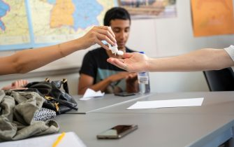 STOCKHOLM, SWEDEN - AUGUST 21: Students share hand sanitizer during class on the first day back to school since the March shut down at the Ostra Real public school on August 21, 2020 in Stockholm, Sweden. The high school will continue a majority of the education online, with physical classes programmed every two weeks. Although Sweden did not experience a total lockdown during the pandemic, contrary to most countries in Europe, with a population of 10 million, it has one of the highest Coronavirus death rates relative to population size in Europe. (Photo by Martin von Krogh/Getty Images)