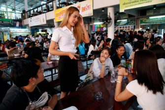 epa08645106 A Thai transgender student Siwakorn Thatsanasorn (C) wearing female university student uniform chats with classmates during a lunch break at a canteen in Thammasat University Rangsit Campus in Pathum Thani province, Thailand, 24 August 2020 (issued 04 September 2020). Outdated regulations at most schools and universities in Thailand mean many transgender people are forced to wear a uniform in class that does not match their gender identity. Since June, Thammasat University has removed those regulations, allowing 20 year-old Siwakorn 'Buzzy' Thatsanasorn to wear the outfit of her choice at school. But Siwakorn says that transgenders in primary and secondary schools are still not allowed to choose gender-appropriate school uniforms.  EPA/RUNGROJ YONGRIT  ATTENTION: This Image is part of a PHOTO SET