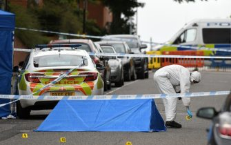"""A police forensics officer gathers evidence near to forensics tents and evidence markers inside a cordon on Irving Street, following a major stabbing incident in the centre of Birmingham, central England, on September 6, 2020. - British police declared a """"major incident"""" early on September 6 after multiple people were stabbed in the centre of England's second city Birmingham. Violence broke out at about 12:30 am (2330 GMT Saturday) in and around the Arcadian Centre, a popular venue filled with restaurants, nightclubs and bars. (Photo by Oli SCARFF / AFP) (Photo by OLI SCARFF/AFP via Getty Images)"""