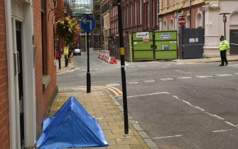 """A police officer stands near to a small forensics tent as he mans a cordon at the junction of Church Street and Barwick Street, following a major stabbing incident in the centre of Birmingham, central England, on September 6, 2020. - British police declared a """"major incident"""" early on September 6 after multiple people were stabbed in the centre of England's second city Birmingham. Violence broke out at about 12:30 am (2330 GMT Saturday) in and around the Arcadian Centre, a popular venue filled with restaurants, nightclubs and bars. (Photo by Oli SCARFF / AFP) (Photo by OLI SCARFF/AFP via Getty Images)"""