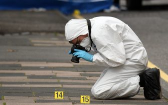 """A police forensics officer takes photographs as he gathers evidence inside a cordon on Irving Street, following a major stabbing incident in the centre of Birmingham, central England, on September 6, 2020. - British police declared a """"major incident"""" early on September 6 after multiple people were stabbed in the centre of England's second city Birmingham. Violence broke out at about 12:30 am (2330 GMT Saturday) in and around the Arcadian Centre, a popular venue filled with restaurants, nightclubs and bars. (Photo by Oli SCARFF / AFP) (Photo by OLI SCARFF/AFP via Getty Images)"""