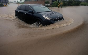epa08651804 A car drives on a flooded road following heavy rain caused by the powerful Typhoon Haishen in Gangneung, South Korea, 07 September 2020.  EPA/YONHAP SOUTH KOREA OUT