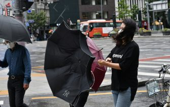 A woman holds her umbrella turned inside out from strong winds caused by Typhoon Haishen in central Seoul on September 7, 2020. - Powerful Typhoon Haishen drenched South Korea on September 7 after slamming southern Japan with record winds and heavy rains that prompted evacuation warnings for millions. (Photo by Jung Yeon-je / AFP) (Photo by JUNG YEON-JE/AFP via Getty Images)