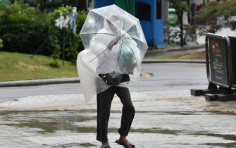 A man struggles to hold onto his umbrella as he walks against strong winds caused by Typhoon Haishen in central Seoul on September 7, 2020. - Powerful Typhoon Haishen drenched South Korea on September 7 after slamming southern Japan with record winds and heavy rains that prompted evacuation warnings for millions. (Photo by Jung Yeon-je / AFP) (Photo by JUNG YEON-JE/AFP via Getty Images)