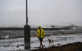 A man walks with his dog along the coastline amid heavy rain in Ichikikushikino, Kagoshima prefecture on September 7, 2020, after Typhoon Haishen passed through. - Powerful Typhoon Haishen approached South Korea on September 7 after slamming southern Japan with record winds and heavy rains that prompted evacuation warnings for millions. (Photo by CHARLY TRIBALLEAU / AFP) (Photo by CHARLY TRIBALLEAU/AFP via Getty Images)