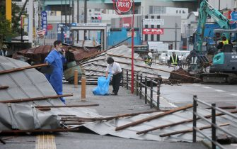 A clean-up crew works to remove roofs which were blown off into a street by strong winds brought by Typhoon Haishen in Fukuoka as the storm passes the southern Japanese island of Kyushu on September 7, 2020. - Powerful Typhoon Haishen approached South Korea on September 7 after slamming southern Japan with record winds and heavy rains that prompted evacuation warnings for millions. (Photo by STR / JIJI PRESS / AFP) / Japan OUT (Photo by STR/JIJI PRESS/AFP via Getty Images)