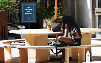 NEW YORK, NEW YORK - SEPTEMBER 07:  A person sitting at an outdoor table works on a laptop near a sign reading 'face coverings are required' during Phase 4 of re-opening following restrictions imposed to slow the spread of coronavirus on September 7, 2020 in New York City. The fourth phase allows outdoor arts and entertainment, sporting events without fans and media production.  (Photo by Cindy Ord/Getty Images)