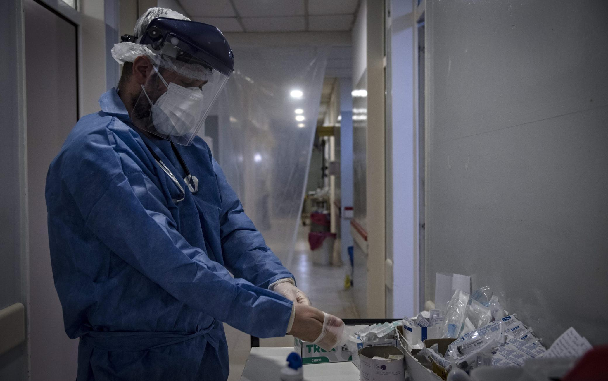 Dr Mario Grossmann wearing protective suit puts on gloves before treating patients with COVID-19, during his 24hs shift, at the emergency area of the Doctor Alberto Antranik Eurnekian Public Hospital in Ezeiza, in the outskirts of Buenos Aires on August 29, 2020, amid the new coronavirus, COVID-19, pandemic. - Dr Grossmann, a professor, head of practical work of semiology and internal medicine at Buenos Aires University (UBA) and chair head of semiology and internal medicine at Universidad Abierta Interamericana (UAI) teaches from the hospital through video calls to students of 4th and 5th year. (Photo by ARIEL TIMY TORRES / AFP) (Photo by ARIEL TIMY TORRES/AFP via Getty Images)
