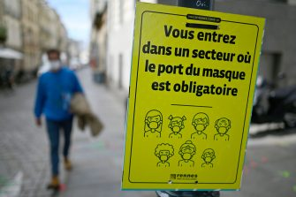 """A city official placard reads in French """"You are entering a face masks required area"""" on September 3, 2020 in Rennes, Brittany, amid the Covid-19 pandemic. (Photo by Damien MEYER / AFP) (Photo by DAMIEN MEYER/AFP via Getty Images)"""