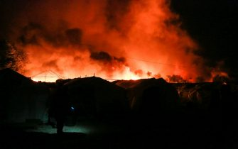 Smoke from a fire rises behind tents inside the Moria migrant camp on the island of Lesbos on September 9, 2020. (Photo by Manolis LAGOUTARIS / AFP) (Photo by MANOLIS LAGOUTARIS/AFP via Getty Images)