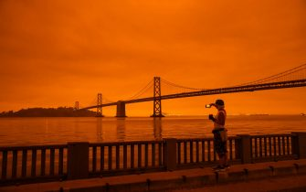 SAN FRANCISCO, CA - SEPTEMBER 09: Amy Scott of San Francisco takes in the view from the Embarcadero as smoke from various wildfires burning across Northern California mixes with the marine layer, blanketing San Francisco in darkness and an orange glow on September 9, 2020 in San Francisco, California.  Over 2 million acres have burned this year as wildfires continue to burn across the state. (Photo by Philip Pacheco/Getty Images)