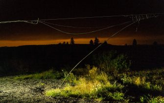OREGON CITY, OR - SEPTEMBER 09: A damaged power line hangs near grass and shrubs as the sky is tinted orange by wildfire smoke in Clackamas County on September 9, 2020 in Oregon City, Oregon. Gov. Kate Brown declared a statewide emergency as blazes grew in several counties. (Photo by David Ryder/Getty Images)