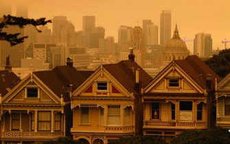 epa08657774 A view of the Painted Ladies, the iconic row of historical Victorian homes with a downtown backdrop, under orange overcast sky in the afternoon in San Francisco, California, USA, 09 September 2020. California wildfire smoke high in the atmosphere over the San Francisco Bay Area blocked the sunlight and turned the sky a dark orange and yellow shade for most of the day.  EPA/JOHN G. MABANGLO