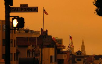 epa08657792 A pedestrian light illuminates a crosswalk on California Street over an orange overcast sky in the afternoon in San Francisco, California, USA, 09 September 2020. California wildfire smoke high in the atmosphere over the San Francisco Bay Area blocked the sunlight and turned the sky a dark orange and yellow shade for most of the day.  EPA/JOHN G. MABANGLO