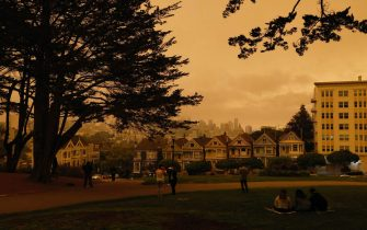 epa08657768 People gather at Alamo Square under an orange and yellow overcast sky overlooking the The Painted Ladies, the iconic row of historical Victorian homes with a downtown backdrop, in the afternoon in San Francisco, California, USA, 09 September 2020. California wildfire smoke high in the atmosphere over the San Francisco Bay Area blocked the sunlight and turned the sky a dark orange and yellow shade for most of the day.  EPA/JOHN G. MABANGLO