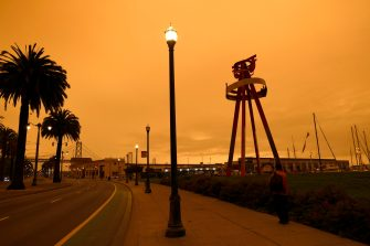 epa08657769 An orange sky in the early afternoon with the San Francisco Bay Bridge in the background as seen from King Street in San Francisco, California, USA, 09 September 2020. California wildfire smoke high in the atmosphere over the San Francisco Bay Area blocked the sunlight and turned the sky a dark orange and yellow shade for most of the day.  EPA/JOHN G. MABANGLO