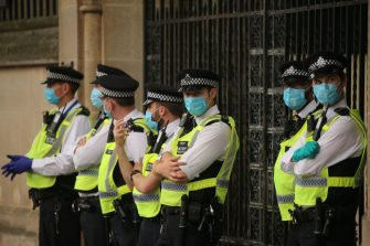 Police officers stand wearing facemasks as a precaution against the transission of novel coronavirus during a demonstration by climate change action group Extinction Rebellion outside the Houses of Parliament in central London on September 9, 2020. (Photo by Isabel Infantes / AFP) (Photo by ISABEL INFANTES/AFP via Getty Images)