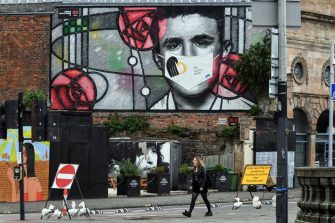 A woman walks beneath a mural of Architect Charles Rennie Mackintosh with an added mask in Glasgow City Centre on September 14, 2020. - Coronavirus rules were tightened Monday, with England and Scotland notably announcing bans on meetings of more than six people from different households. (Photo by Andy Buchanan / AFP) (Photo by ANDY BUCHANAN/AFP via Getty Images)