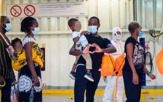 "A rescued migrant carrying a baby as he stands in line forms a heart with his hands before leaving the Sea-Watch 4 rescue ship to board a ferry on which some 350 migrants will be under quarantine, off the coast of Palermo, Sicily, Italy, on September 02, 2020. - More than 350 migrants including those rescued by a vessel sponsored by British street artist Banksy were being transferred onto a quarantine vessel off Sicily. ""The first people have boarded the quarantine vessel and the operation is ongoing,"" Mattea Weihe, spokeswoman for the Sea-Watch humanitarian organisation told AFP. (Photo by Thomas Lohnes / AFP) / Germany OUT"