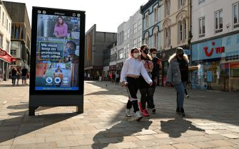 "Pedestrians and shoppers, some wearing a face mask or coverings, walk past a an electronic billboard asking members of the public to follow the UK Government's guidelines to help mitigate the spread of COVID-19 in Newcastle city centre, north-east England, on September 17, 2020. - The British government on Thursday announced new restrictions for northeast England, the latest region to see a surge in coronavirus cases as Prime Minister Boris Johnson warned of a ""second hump"" in nationwide transmission. Residents in the northeast, which includes the cities of Newcastle and Sunderland, will no longer be allowed to socialise outside their own homes or support bubble from Friday onwards. (Photo by Oli SCARFF / AFP) (Photo by OLI SCARFF/AFP via Getty Images)"