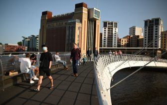 "People walk across the Millennium Bridge on the River Tyne in the early evening sunshine in Newcastle upon Tyne, north-east England, on September 17, 2020. - The British government on Thursday announced new restrictions for northeast England, the latest region to see a surge in coronavirus cases as Prime Minister Boris Johnson warned of a ""second hump"" in nationwide transmission. Residents in the northeast, which includes the cities of Newcastle and Sunderland, will no longer be allowed to socialise outside their own homes or support bubble from Friday onwards. (Photo by Oli SCARFF / AFP) (Photo by OLI SCARFF/AFP via Getty Images)"
