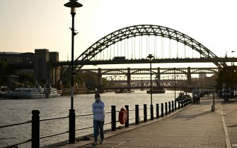 "A woman wearing a protective face mask walks along the quayside, on the banks of the River Tyne, backdropped by the Tyne Bridge in Newcastle, north-east England, on September 17, 2020. - The British government on Thursday announced new restrictions for northeast England, the latest region to see a surge in coronavirus cases as Prime Minister Boris Johnson warned of a ""second hump"" in nationwide transmission. Residents in the northeast, which includes the cities of Newcastle and Sunderland, will no longer be allowed to socialise outside their own homes or support bubble from Friday onwards. (Photo by Oli SCARFF / AFP) (Photo by OLI SCARFF/AFP via Getty Images)"