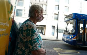 NEWCASTLE UPON TYNE, ENGLAND - SEPTEMBER 17: A woman wearing a face mask waits for a bus in Newcastle on September 17, 2020 in Newcastle upon Tyne, England. Almost two million people in north-east England will be banned from mixing with other households and pubs will close early as coronavirus cases rise. Health Secretary Matt Hancock announced the temporary restrictions will be in place from midnight due to concerning rates of infection. The measures affect seven council areas, Newcastle, Northumberland, North Tyneside, South Tyneside, Gateshead, County Durham and Sunderland. (Photo by Ian Forsyth/Getty Images)