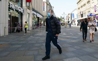 NEWCASTLE UPON TYNE, ENGLAND - SEPTEMBER 17: A man wearing a face mask walks through Newcastle city centre on September 17, 2020 in Newcastle upon Tyne, England. Almost two million people in north-east England will be banned from mixing with other households and pubs will close early as coronavirus cases rise. Health Secretary Matt Hancock announced the temporary restrictions will be in place from midnight due to concerning rates of infection. The measures affect seven council areas, Newcastle, Northumberland, North Tyneside, South Tyneside, Gateshead, County Durham and Sunderland. (Photo by Ian Forsyth/Getty Images)