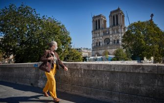 PARIS, FRANCE - SEPTEMBER 14: A Parisian walks past Notre Dame Cathedral in Paris, where wearing a face mask in public is compulsory since the recent surge of COVID-19 cases in the city on September 14, 2020 in Paris, France. On Saturday, the number of new daily cases exceeded 10,000, with infection rates rising among all age groups. (Photo by Kiran Ridley/Getty Images)