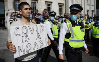epa08681147 A protester holds a banner by police during a 'Resist & Act For Freedom Rally'  demonstration in London, Britain, 19 September 2020. The rally run by suspended former nurse Kate Shemirani is a forum for people who believe the Covid virus is a hoax and are anti-vaccine and government intervention.  EPA/NEIL HALL