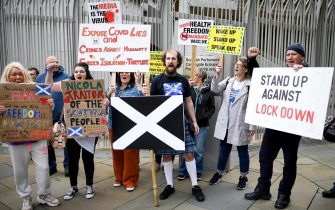"""EDINBURGH, SCOTLAND - SEPTEMBER 10: Protesters holding placards gather outside the Scottish Parliament entrance to demonstrate against a secondary lockdown, coronavirus face covering rules and the search for a virus on September 10, 2020 in Edinburgh, Scotland. The group, known as Saving Scotland, said it is """"time to stand up together"""" and fight """"for the freedom to choose"""" and listen to real scientific evidence in regard to the health of the Scottish people. (Photo by Jeff J Mitchell - Pool/Getty Images)"""