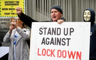 """EDINBURGH, SCOTLAND - SEPTEMBER 10: A protester holds a sign that reads 'stand up against lockdown' outside the Scottish Parliament entrance to demonstrate against a secondary lockdown, coronavirus face covering rules and the search for a virus on September 10, 2020 in Edinburgh, Scotland. The group, known as Saving Scotland, said it is """"time to stand up together"""" and fight """"for the freedom to choose"""" and listen to real scientific evidence in regard to the health of the Scottish people. (Photo by Jeff J Mitchell - Pool/Getty Images)"""