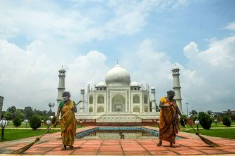 Workers clean around a replica of the Taj Mahal within the premises of an amusement park during a new lockdown imposed by the state government against the surge in COVID-19 coronavirus cases, in Kolkata on July 29, 2020. (Photo by Dibyangshu SARKAR / AFP) (Photo by DIBYANGSHU SARKAR/AFP via Getty Images)