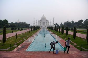 Workers clean the ground at the Taj Mahal in Agra on September 21, 2020. - The Taj Mahal reopened to visitors on September 21 in a symbolic business-as-usual gesture even as India looks set to overtake the US as the global leader in coronavirus infections. (Photo by Sajjad HUSSAIN / AFP) (Photo by SAJJAD HUSSAIN/AFP via Getty Images)