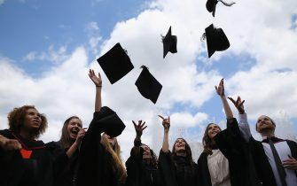 LONDON, ENGLAND - JULY 15:  Students throw their caps in the air ahead of their graduation ceremony at the Royal Festival Hall on July 15, 2014 in London, England. Students of the London College of Fashion, Management and Science and Media and Communication attended their graduation ceremony at the Royal Festival Hall today.  (Photo by Dan Kitwood/Getty Images)