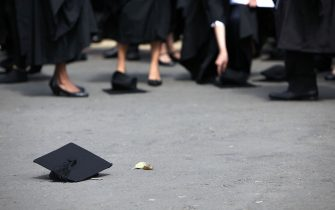 BIRMINGHAM, ENGLAND - JULY 14:  Students pick up their mortarboards after the offical hat throwing photograph at the University of Birmingham on July 14, 2009 in Birmingham, England. Over 5000 graduates will be donning their robes this week to collect their degrees from The University of Birmingham. A recent survey suggested that there are 48 graduates competing for every job.  (Photo by Christopher Furlong/Getty Images)