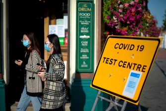Pedestrians wearing facemasks walks past a sign for a Covid-19 test centre in Leyton, east London on September 19, 2020. (Photo by DANIEL LEAL-OLIVAS / AFP) (Photo by DANIEL LEAL-OLIVAS/AFP via Getty Images)