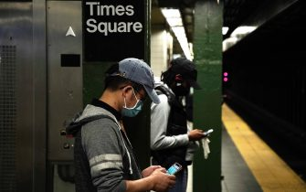 NEW YORK, NEW YORK - SEPTEMBER 22: People with cell phones wear protective masks while waiting for a subway train during Phase 4 of re-opening following restrictions imposed to slow the spread of coronavirus on September 22, 2020 in New York City . The fourth phase allows outdoor arts and entertainment, sporting events without fans and media production. (Photo by John Lamparski/Getty Images)