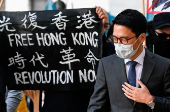"""Hong Kong democracy activist Nathan Law stands next to a banner reading """"Free Hong Kong. Revolution now"""" as he attends a demonstration on September 1, 2020 outside the Foreign Office in Berlin, where the Chinese Foreign Minister was expected to hold talks with his German counterpart. (Photo by Tobias SCHWARZ / AFP) (Photo by TOBIAS SCHWARZ/AFP via Getty Images)"""